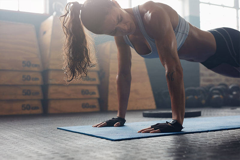 strong brunette woman doing push-ups
