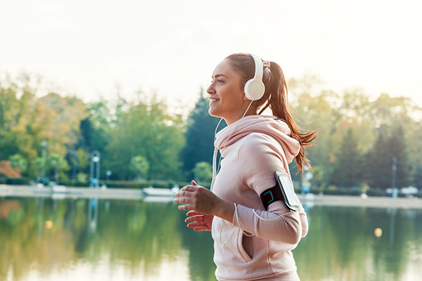 woman running outside with headphones | motivate yourself to work out