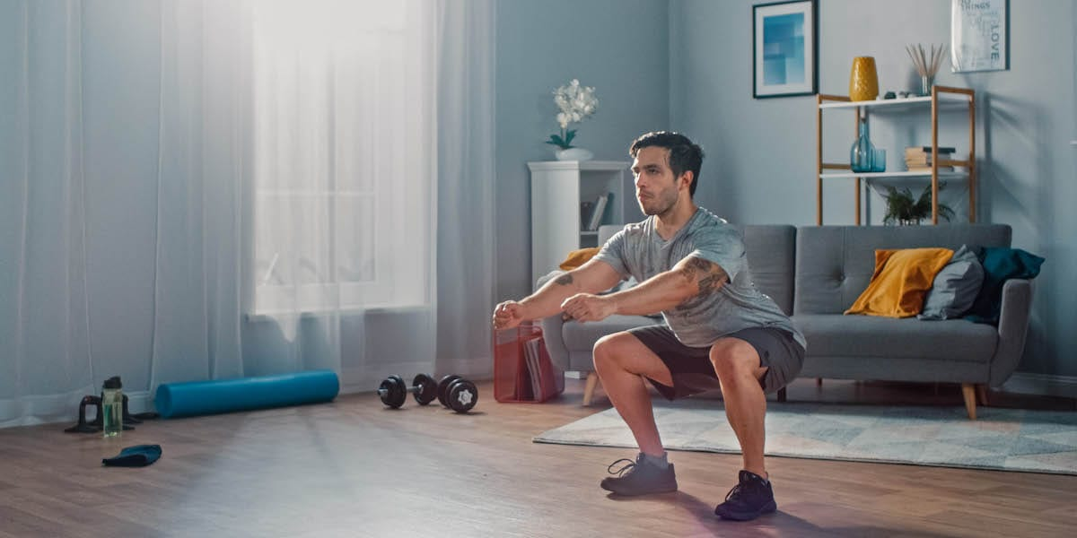 bodyweight myths - man doing squats at home
