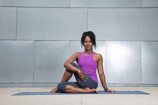 woman on yoga mat in Half Lord of The Fishes pose