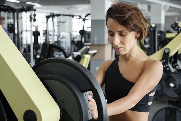woman adding weights to bar | workout plateau