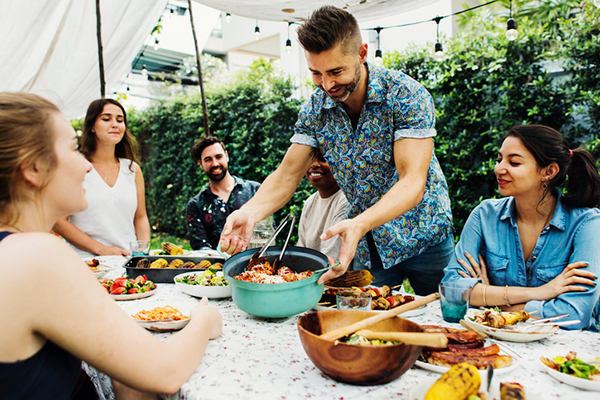 man placing food down during potluck   thanksgiving cant cook
