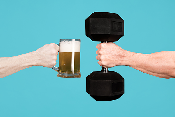 mug of beer and dumbbell being held up | exercise and alcohol