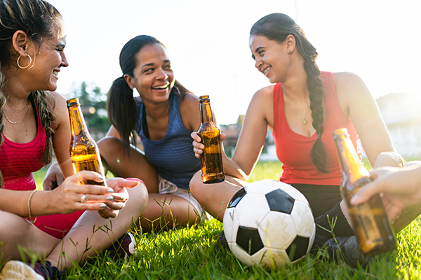 women sharing drinks after soccer game | exercise and alcohol
