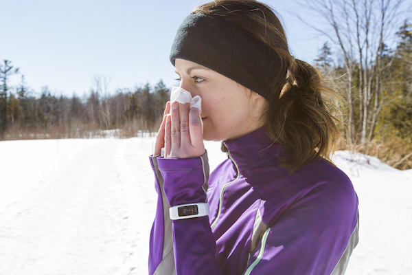 working out when sick- woman blowing nose