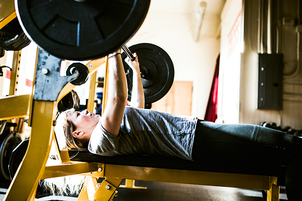 Woman doing benchpress - strength training program