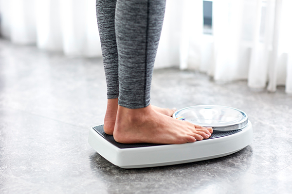 woman weighing herself on scale | how to gain weight