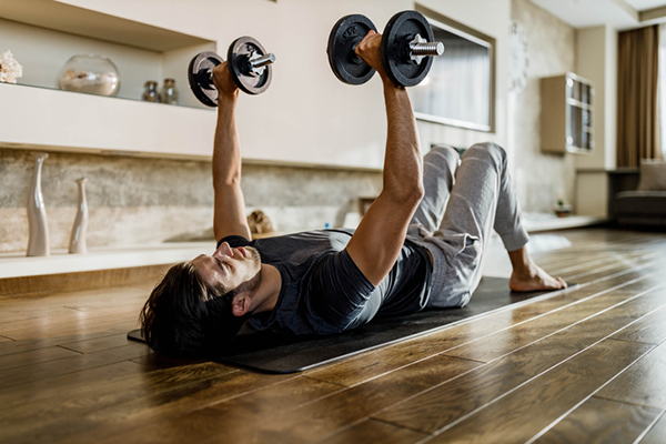 man doing floor press at home | how to gain weight
