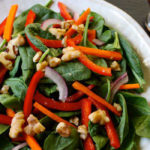 Spinach salad recipe with walnuts, carrots, and red bell peppers