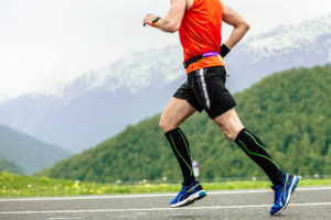 man running wearing compression socks -- does compression clothing wear work