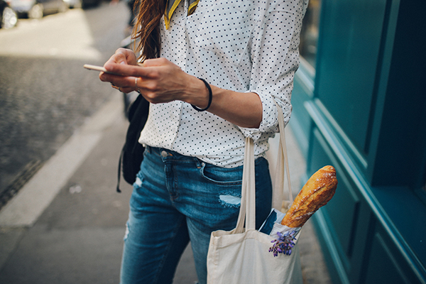 Woman texting with a shopping bag on her arm