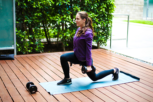 Woman doing lunges with weights outside