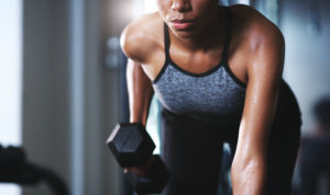 woman doing a weighted row -- how do you build muscle -- weightlifting for beginners