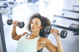 woman lifting dumbbells -- weightlifting for beginners
