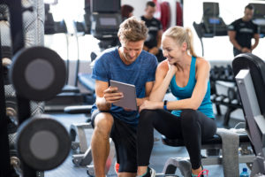 woman setting goals with personal trainer -- what's your weight training goal -- weightlifting for beginners