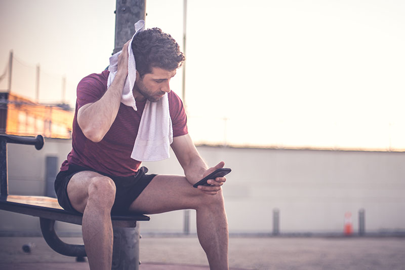 Why Men Lose Weight Faster Than Women, man looking at his phone after exercising