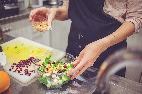 Woman adding toppings to a salad