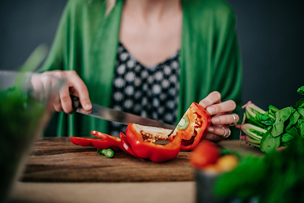 Woman chopping red bell peppers