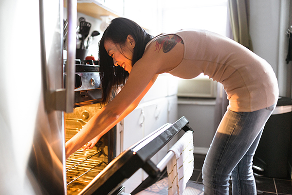 Woman putting food in oven