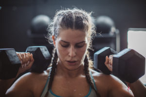 woman lifting two heavy dumbbells -- weightlifting myths