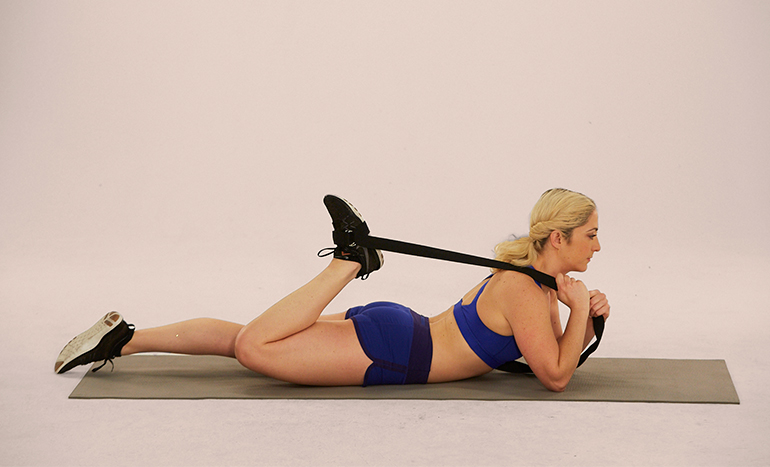 woman on exercise mat performing lying prone quad stretch with strap