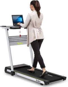 Woman using a walking treadmill desk to do work on her laptop.