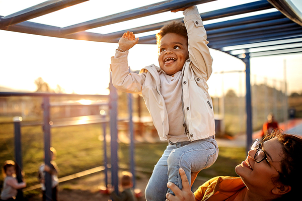 mom helping son on monkey bars   find time to work out