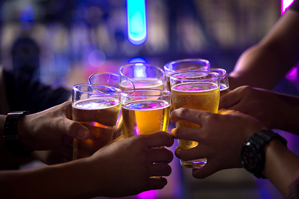people holding glasses of beer together | hangover recovery