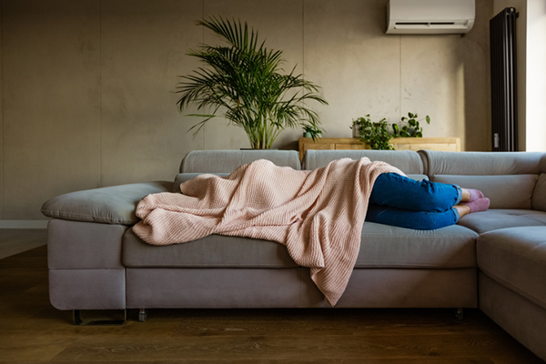 woman lying on couch covered with blanket | hangover recovery