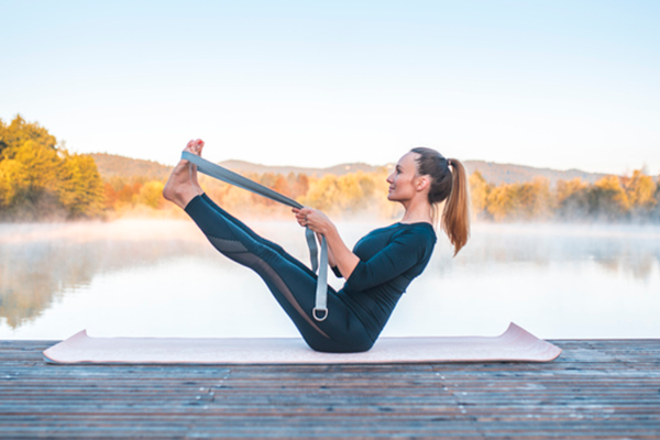 woman doing navasana with yoga strap   boat pose