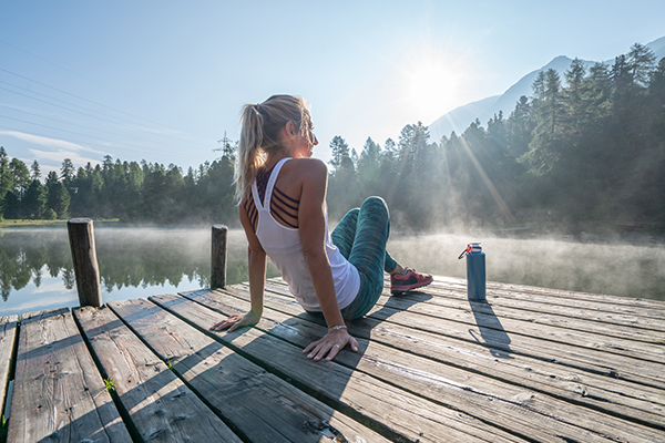 woman on a lake dock | benefits of quitting drinking