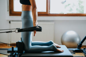 Woman using a pilates reformer on a rest day