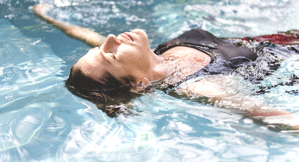 benefits of swimming- woman relaxing in pool