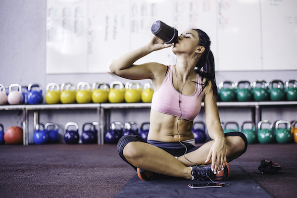 cardio for beginners- woman drinking water at the gym