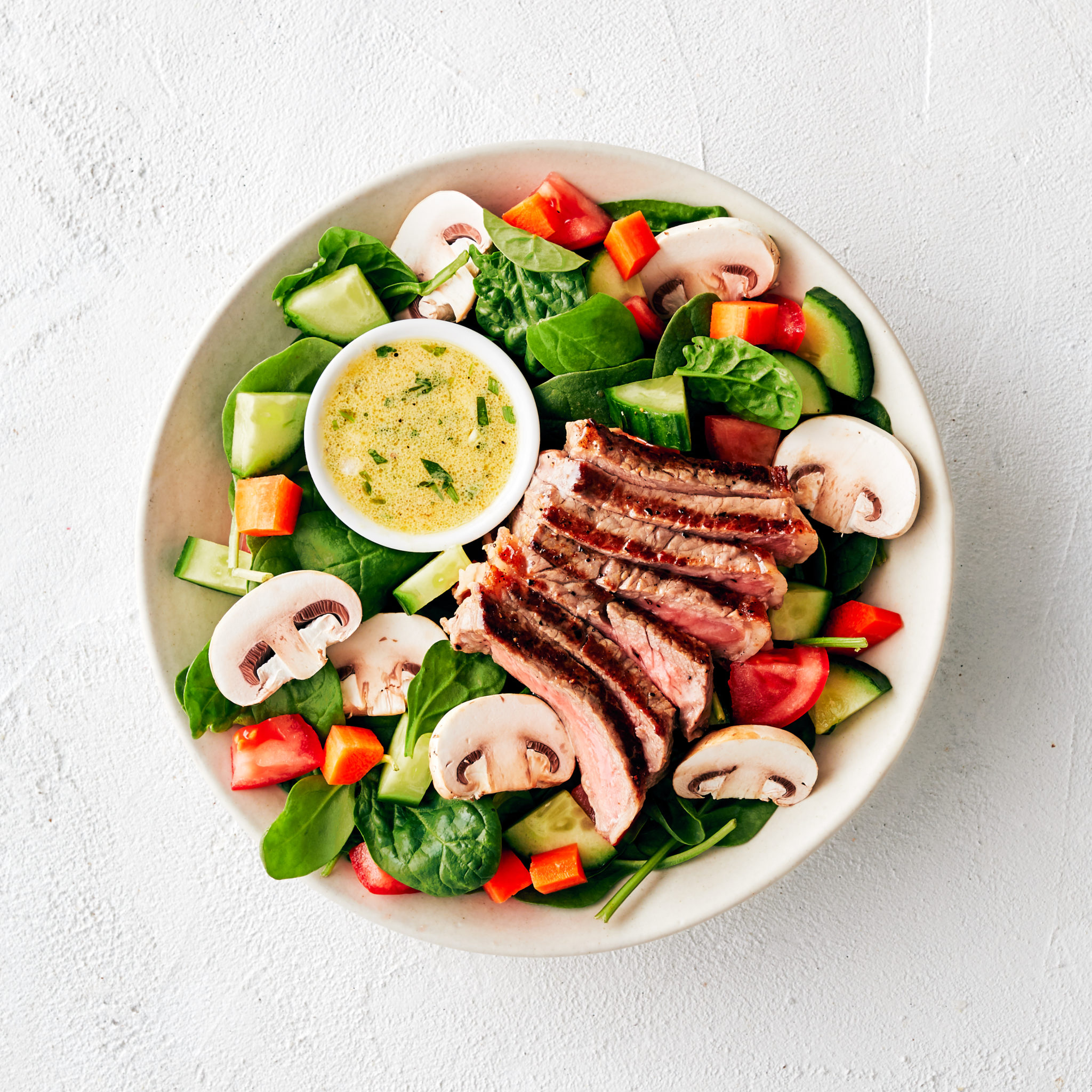 aerial view of a while bowl of steak salad with lemon tarragon vinaigrette