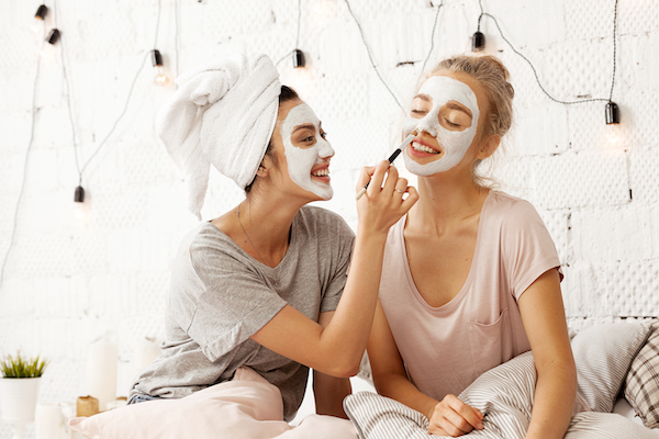 two women in Pjs on a bed with face masks on