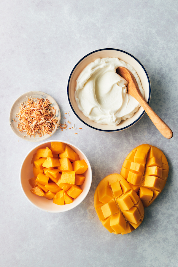 Greek yogurt mango snack with a bowl of yogurt and mango cut into cubes