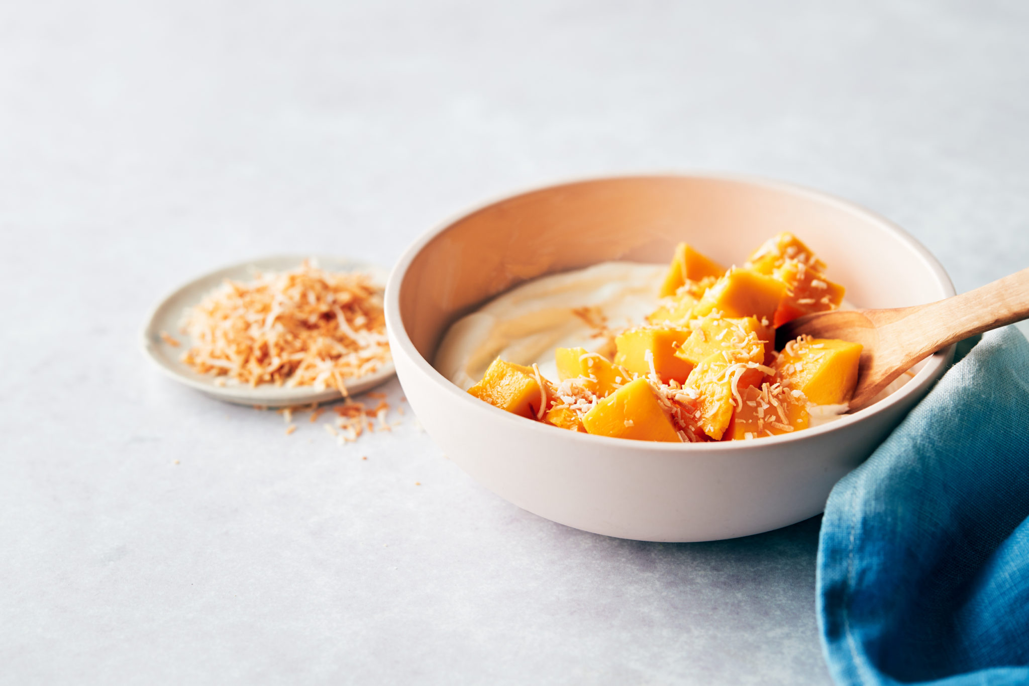 bowl of Greek yogurt with a stack of mango cubes on top and shredded coconut