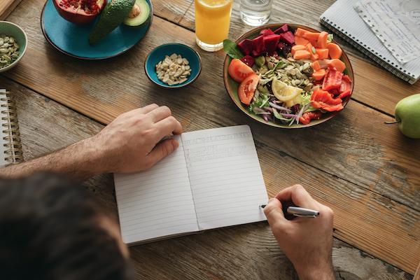 man writing in journal with a vegan meal in front of him