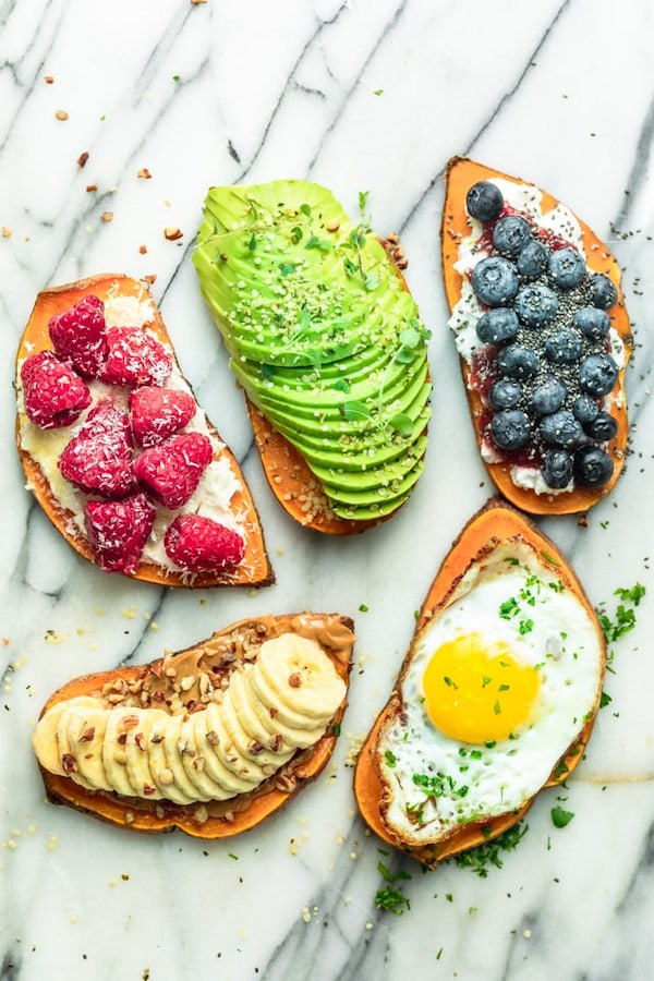 5 slices of sweet potato toast with different toppings, raspberry, avocado, blueberries, fried egg and banana