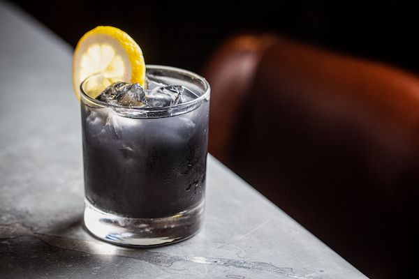 glass of Blackened Lemonade fall mocktail with slice of lemon on the edge on granite surface