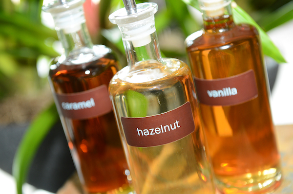 3 glass bottles of hazelnut, vanilla and caramel syrups