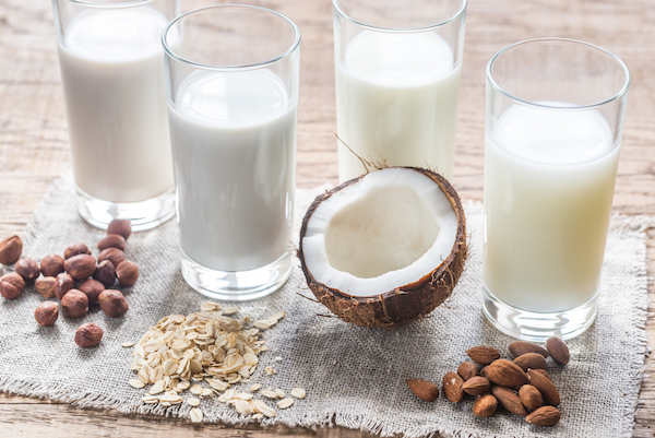 4 glasses of hazelnut, oat, coconut and almond milk with their ingredients in front of the glass