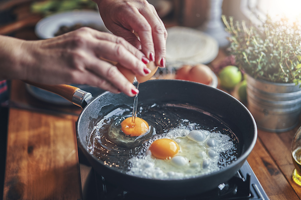 health myths - woman's hands frying 2 eggs in a pan