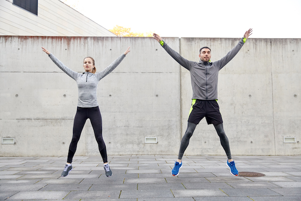 man and woman performing jumping jacks outside