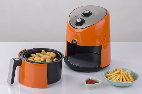 orange and black air fryer with chicken strips and a bowl of fried next to it