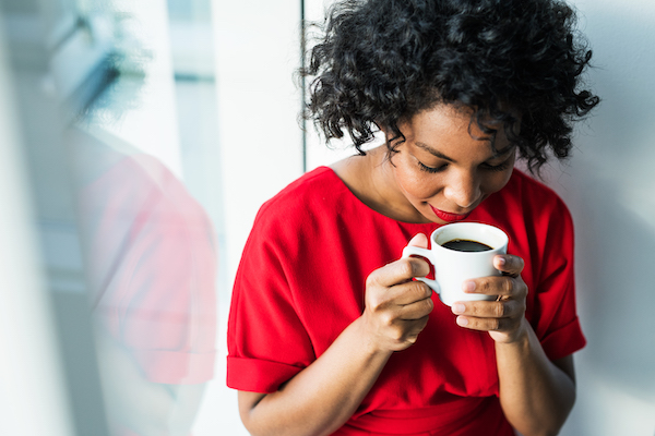 woman dressed in red dress sitting against a window sniffing a cup of coffee