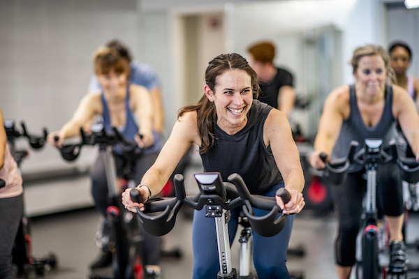 women at an indoor cycling class
