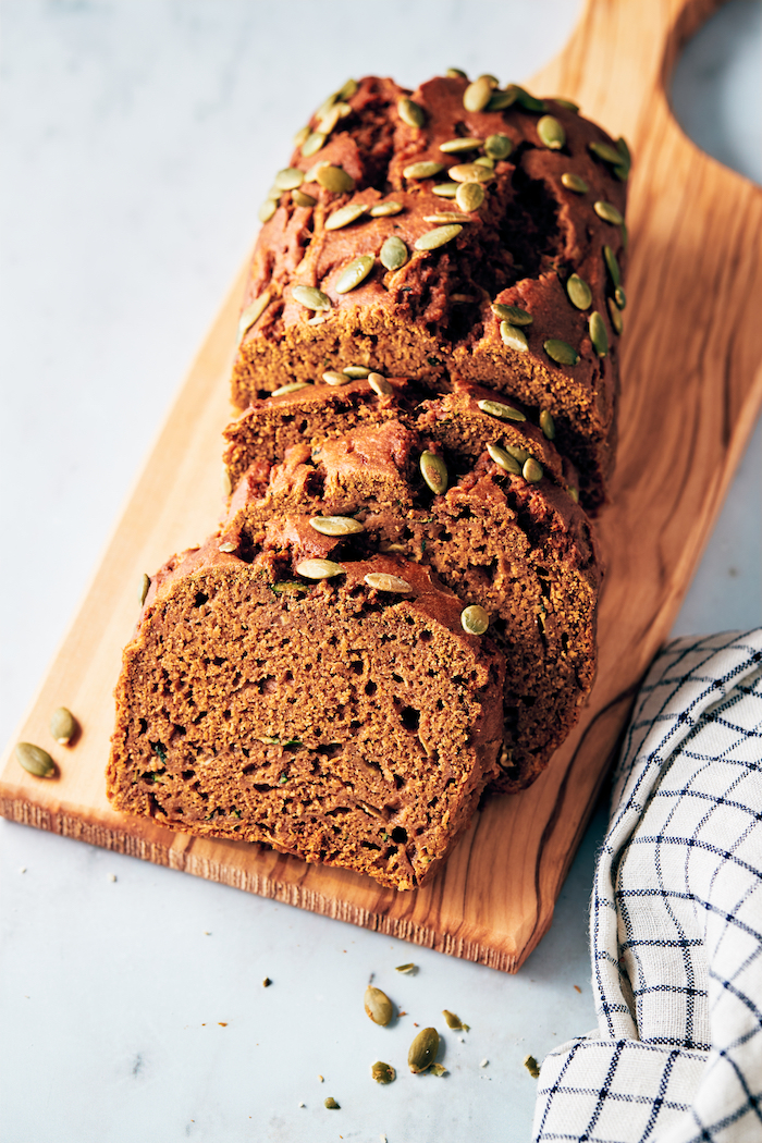 slices of pumpkin zucchini bread on a wooden chopping board
