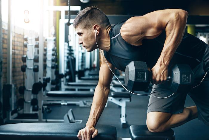 Construcción de músculos del brazo- hombre en el gimnasio
